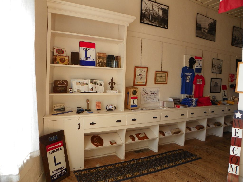 Wooden shelving painted white with Lincoln Highway historical artifacts and merchandise