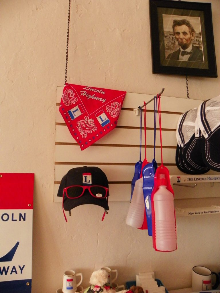 Lincoln Highway merchandise, a hat, bandana, sunglasses, and water bottles for pets