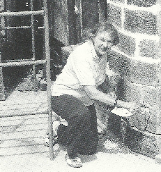 LHA President Esther Oyster kneels next to the 1860 H. I. Lincoln Building for a tuckpointing repair