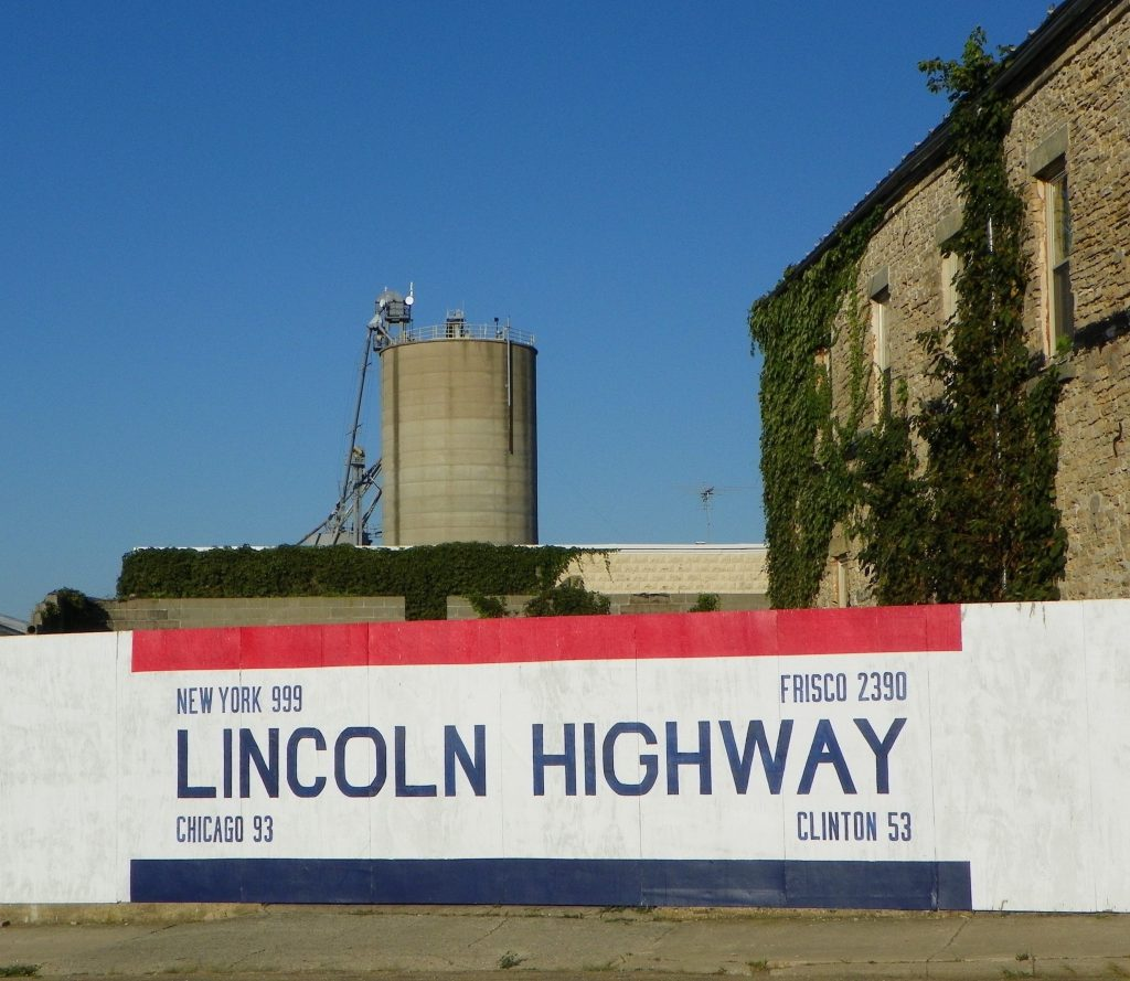 The Lincoln Highway Mileage sign in Franklin Grove is painted on a white picket fence with red and blue. It is 999 miles to New York, 2,330 miles to San Francisco, 93 miles to Chicago, and 53 miles to Clinton, Iowa.
