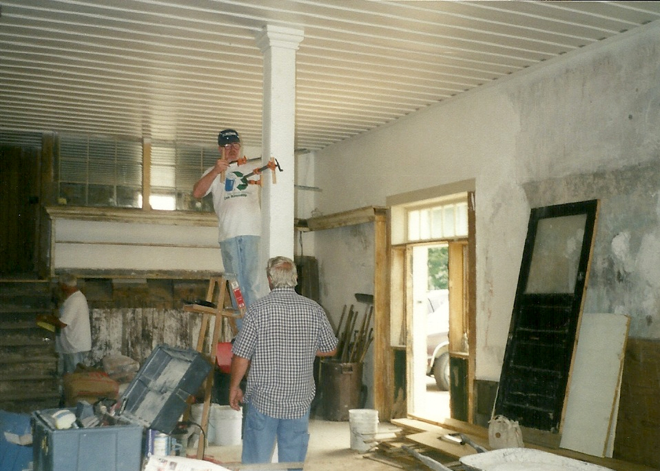 Workers inside the first floor of the building.  The ceiling already has a fresh coat of paint